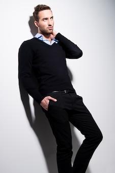 Mode portret van jonge man in zwarte trui en blauw shirt met contrast schaduwen