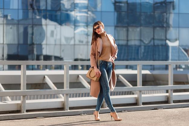 Mode portret van jonge model vrouw in mooie bruine beige jas, denim jeans en zonnebril op stedelijke achtergrond.