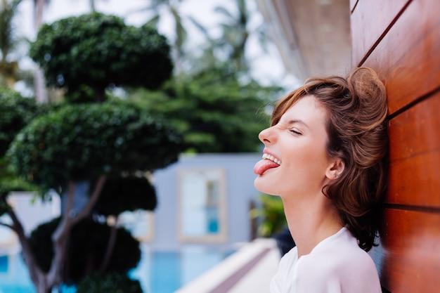 Mode portret van jonge mooie stijlvolle vrouw in wit licht zomerjurk en grote zwarte massieve laarzen op rijke luxevilla