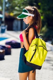 Mode portret van jonge mooie vrouw in stijlvolle sport uniform met neon rugzak en transparant vizier poseren buiten in zonnige zomerdag.