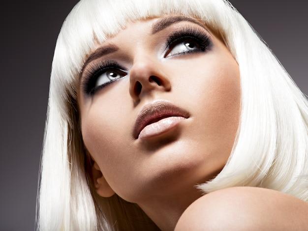 Mode portret van jonge mooie vrouw met witte haren en zwarte make-up van oog