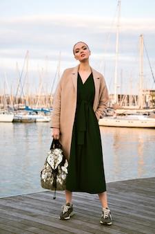 Mode portret van jonge prachtige elegante vrouw poseren promenade, jurk jas sneakers en rugzak, luxe toeristische, zachte warme kleuren dragen.