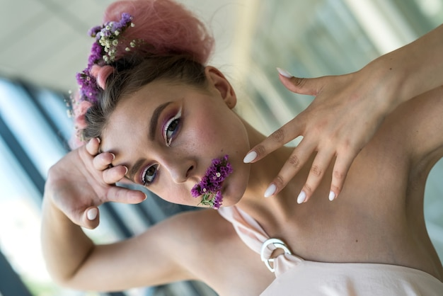 Mode portret van jonge vrouw met bloemen in haar mond
