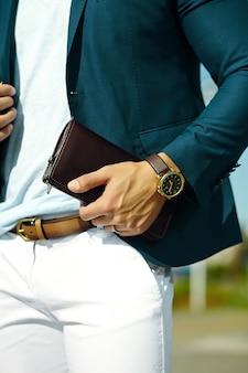 Mode portret van jonge zakenman knappe model man in casual doek pak met accessoires op handen