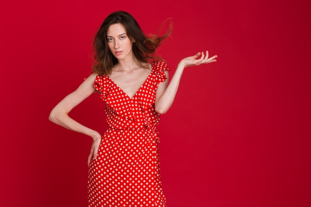 Mode portret van lachende jonge vrouw in rode gestippelde jurk op rood
