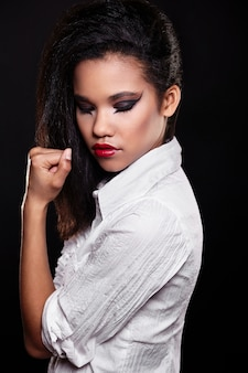 Mode portret van mooie amerikaanse zwarte vrouwelijke brunette meisje model met lichte make-up rode lippen in wit shirt.