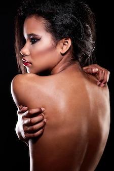Mode portret van mooie amerikaanse zwarte vrouwelijke brunette meisje model met lichte make-up rode lippen naakt terug.