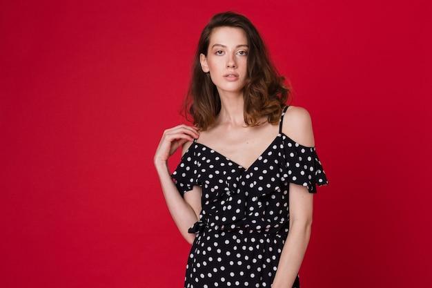 Mode portret van mooie jonge vrouw in zwarte gestippelde jurk op rode studio