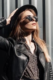 Mode portret van mooie jonge vrouw met zwarte bril en modieuze hoed met vintage jurk en casual leren jas buiten op een zonnige dag