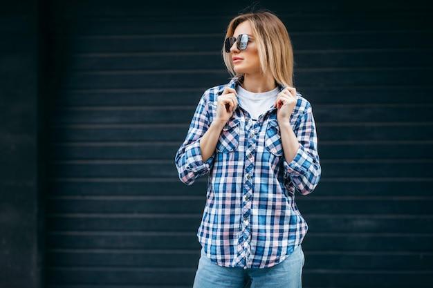 Mode portret van mooie vrouw met mooi gezicht, gekleed in grunge geruite overhemd poseren alleen