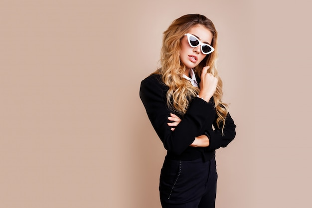 Mode portret van prachtige blonde vrouw in stijlvolle casual zwarte jas poseren op beige muur. witte retro bril. hight fashion look.