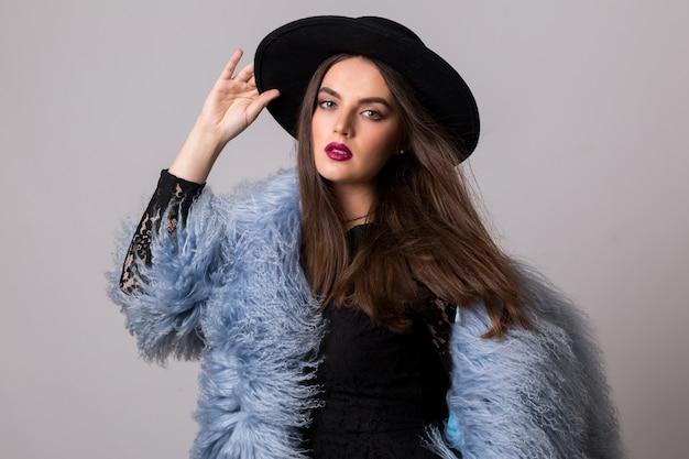 Mode portret van prachtige vrouw in stijlvolle winter pluizige blauwe jas en zwarte hoed poseren op helder grijze muur.