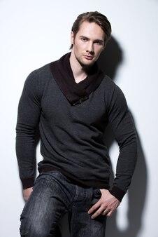 Mode portret van sexy jonge man in casual poses over muur met contrast schaduwen