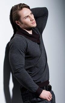 Mode portret van sexy jonge man met hand in de buurt van gezicht in casual poses over muur met contrast schaduwen.