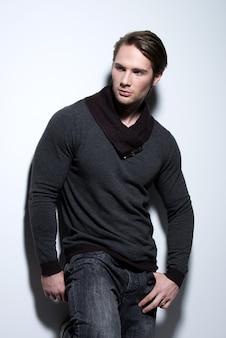 Mode portret van sexy knappe man in grijze trui vormt over muur met contrast schaduwen en zijwaarts op zoek.