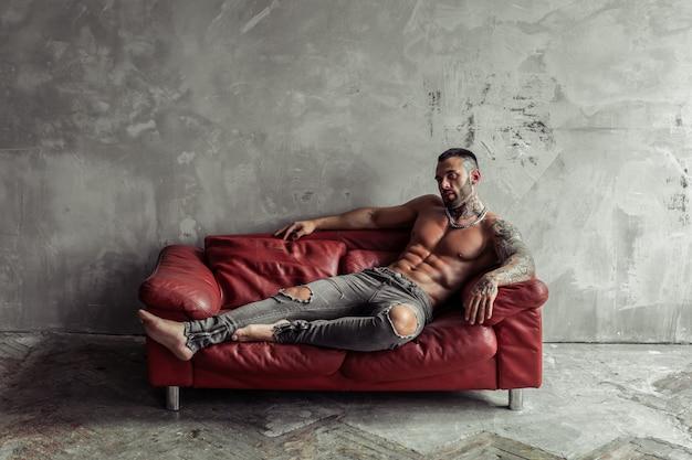 Mode portret van sexy naakt mannelijk model met tatoeage en een zwarte baard liggend in hete pose op rode lederen bank. loft kamer interieur met grijze betonnen muur.