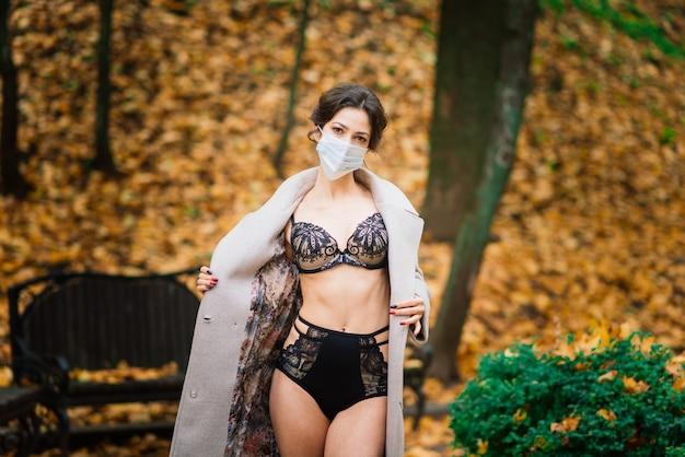 Mode portret van sexy vrouw in gezichtsmasker en een romper in herfst park. pandemie, virus, coronavirus
