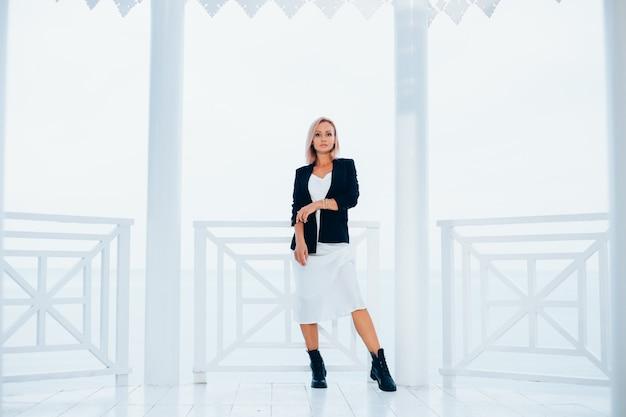 Mode portret van stijlvolle blanke vrouw in zijden lange jurk zwarte blazer en grote laarzen in luxe plek met uitzicht op zee