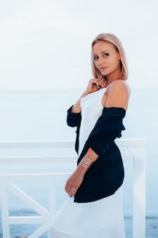 Mode portret van stijlvolle blanke vrouw in zijden lange jurk zwarte blazer op luxe plek met uitzicht op zee