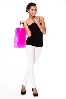 Mode portret van stijlvolle glimlachende casual jonge vrouwelijke mooie zwarte amerikaanse meid met boodschappentassen tegen een witte achtergrond