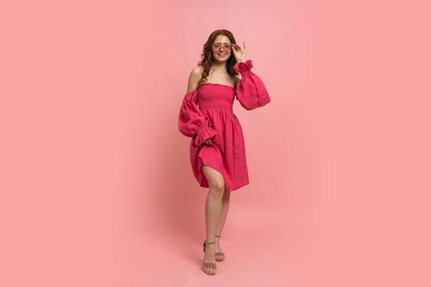 Mode portret van stijlvolle roodharige vrouw poseren op roze lien jurk met mouwen op roze