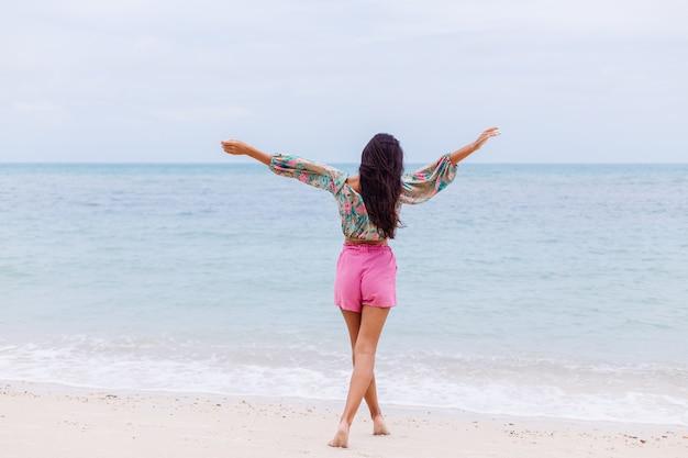 Mode portret van stijlvolle vrouw in kleurrijke print top met lange mouwen en roze broek op strand, tropische achtergrond.