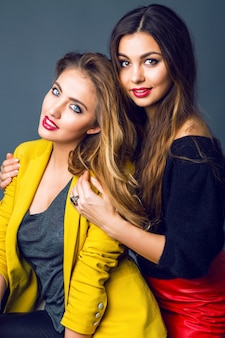 Mode portret van twee geweldige mooie blonde en brunette vrouwen, heldere rokerige make-up en stijlvolle slimme vrijetijdskleding dragen.