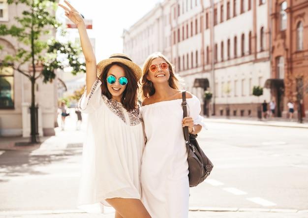 Mode portret van twee jonge stijlvolle hippie brunette en blonde vrouwen modellen in zonnige zomerdag in witte hipster kleding poseren. geen make-up
