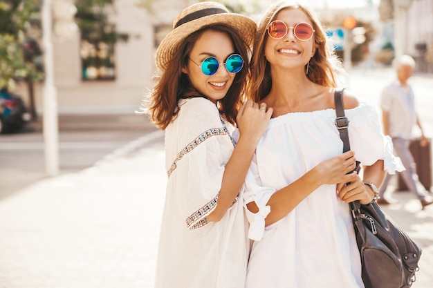 Mode portret van twee jonge stijlvolle hippie brunette en blonde vrouwen modellen in zonnige zomerdag in witte hipster kleding poseren