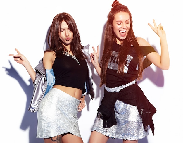 Mode portret van twee lachende brunette modellen in zomer casual hipster kleding op wit wordt geïsoleerd