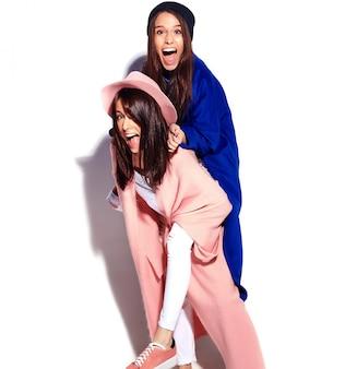 Mode portret van twee lachende brunette vrouwen modellen in zomer casual hipster overjas geïsoleerd op wit. meisjes houden elkaar achterop