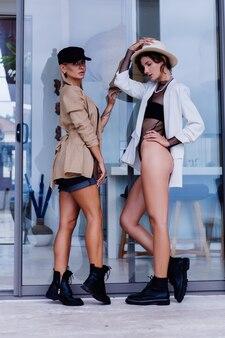 Mode portret van twee stijlvolle blanke vrouw in blazers franse pet en klassieke witte hoedenstandaard
