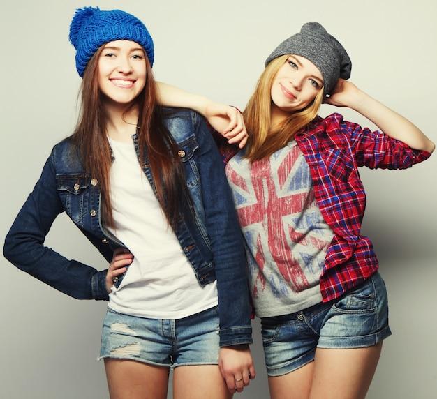 Mode portret van twee stijlvolle sexy hipster meisjes beste vrienden, met schattige swag outfits en hoeden. over grijze achtergrond.