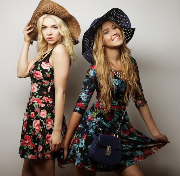 Mode portret van twee stijlvolle sexy meisjes beste vrienden, gekleed in jurk en hoeden. gelukkige tijd voor plezier.