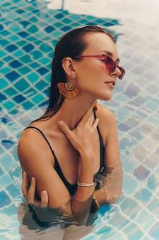 Mode portret van verleidelijke sierlijke vrouw in stijlvolle gele oorbellen met perfecte lichaam poseren in het zwembad tijdens vakanties op luxe resort.