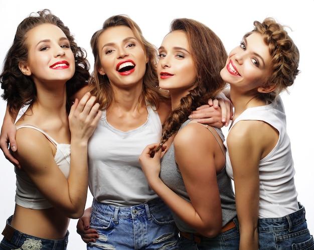 Mode portret van vier stijlvolle sexy hipster meisjes beste vrienden, over grijze achtergrond. gelukkige tijd voor plezier.