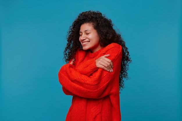 Mode portret van vrouw, gekleed in warme oversized rode gebreide trui, knuffelt zichzelf strak met handen