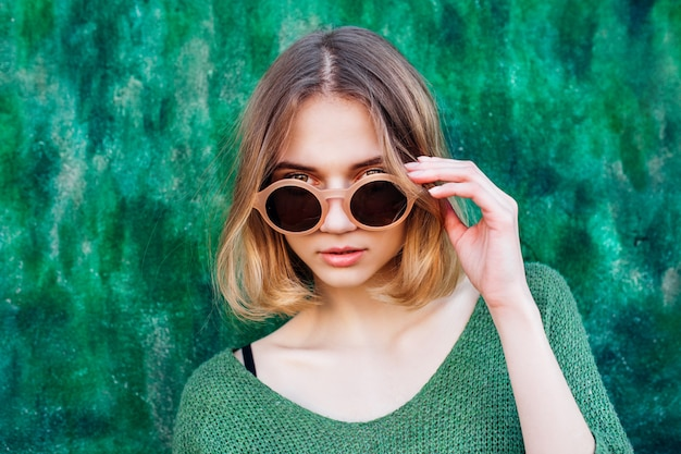 Mode portret van vrouw in sunglsees. mooie jonge vrouwen smaragdgroene sweater op groene muur