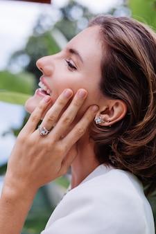 Mode portret van vrouw in tropische luxevilla, gekleed in witte stijlvolle blazer en sieraden over tropische bladeren