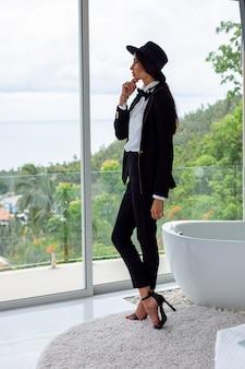 Mode portret van vrouw in zwart pak, vlinderdas en hoed bij luxevilla