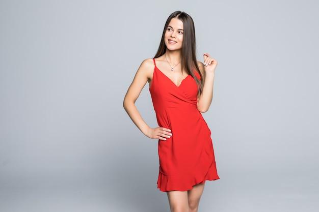 Mode portret van vrouw met lang haar in rode jurk geïsoleerd op een grijze muur.