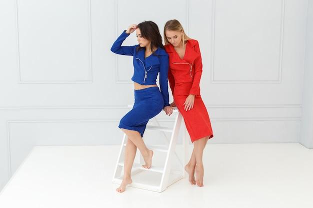 Mode portret van vrouwen in rode en blauwe pakken