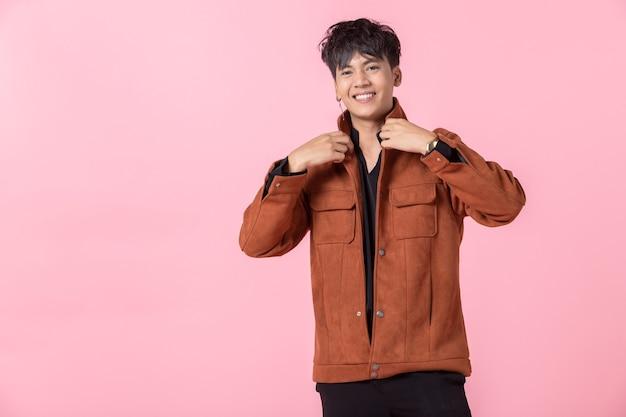 Mode portret van zelfverzekerde knappe jonge aziatische man met het houden van handen in de zakken van de zak de zijogen camera kijken in geïsoleerde op roze lege kopie ruimte studio achtergrond.