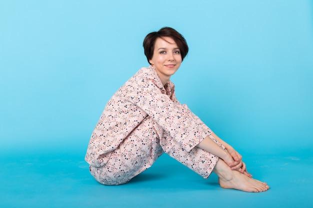 Mode portret vrij cool meisje in huis dragen pyjama met plezier op blauwe achtergrond. ontspan lekker