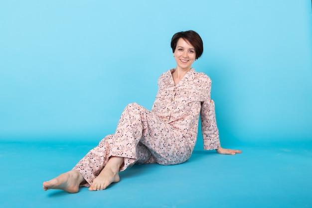 Mode portret vrij cool meisje in huis dragen pyjama met plezier op blauwe achtergrond.