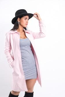 Mode portret vrouw trendy lange roze jas dragen.