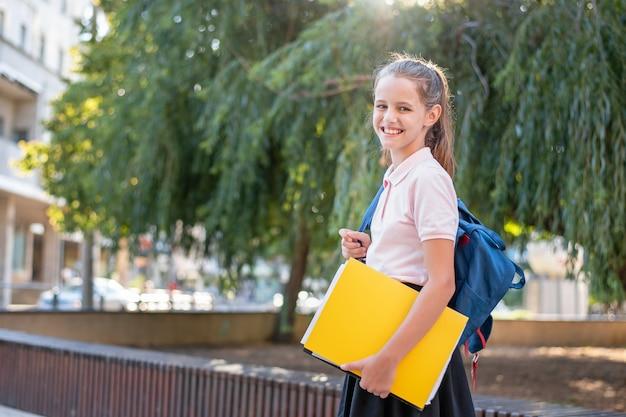 Mode poschoolgirl met een rugzak en een map smilingrtrait van een mooie jonge halfbloedvrouw.