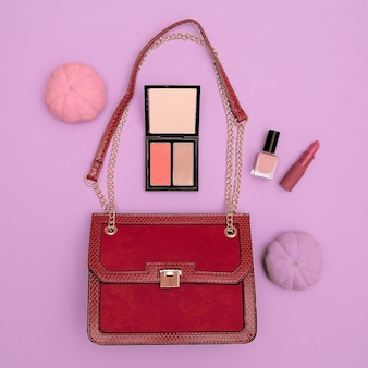 Mode rode dames clutch en cosmetica op roze achtergrond. platliggend stijlconcept