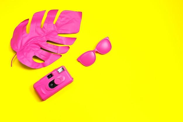 Mode roze zonnebril en camera. tropisch blad