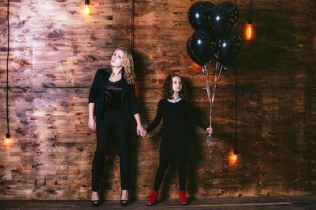 Mode schattig klein meisje en mooie vrouw met een bos van zwarte ballonnen tegen de muur met lampen